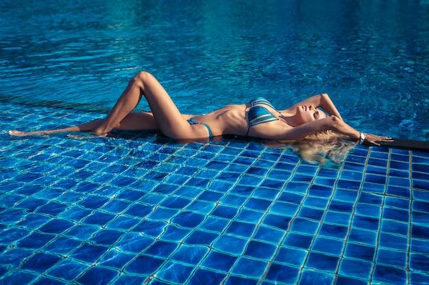 Joven modelo sexy en bikini azul posando en la piscina. agua azul fresca cuerpo delgado.