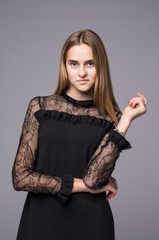 Joven modelo en vestido de moda posando sobre fondo gris