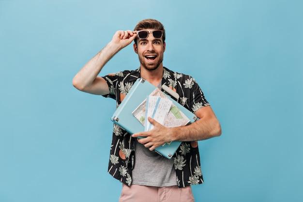Joven moderno con barba pelirroja en ropa de verano pintada quitándose las gafas de sol y sosteniendo, maleta azul, mapa y boletos