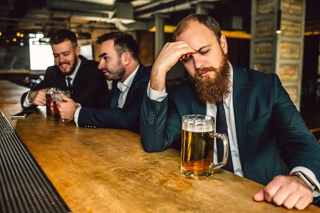 Joven molesto y cansado sentarse t barra de bar. él mira hacia abajo y toma la mano en la frente. jarra de cerveza en la barra de bar. otros dos jóvenes se sientan detrás.