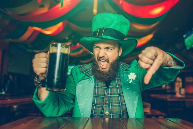 Joven molesto y disgustado en traje verde pose. se sienta a la mesa en el pub y muestra el pulgar hacia abajo. joven sostenga la taza de cerveza oscura.