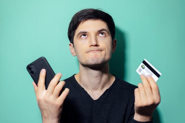 Joven molesto mirando hacia arriba sosteniendo en las manos smartphone y tarjeta de crédito en la pared de color aqua menthe.
