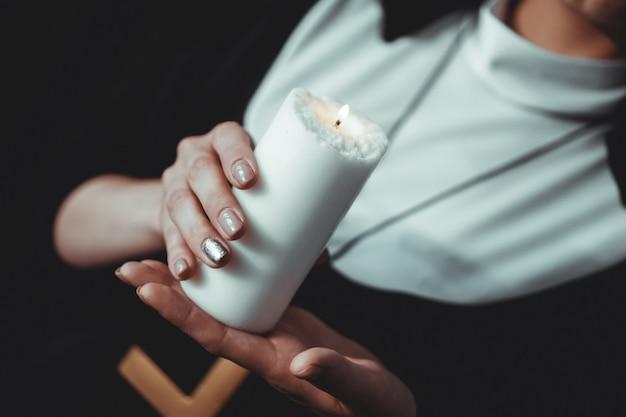 La joven monja católica sostiene una vela en sus manos. foto sobre fondo negro. vista lateral.