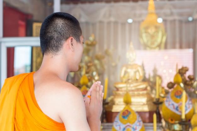 El joven monje ora de acuerdo con la ordenanza, el sacerdote está orando rutina