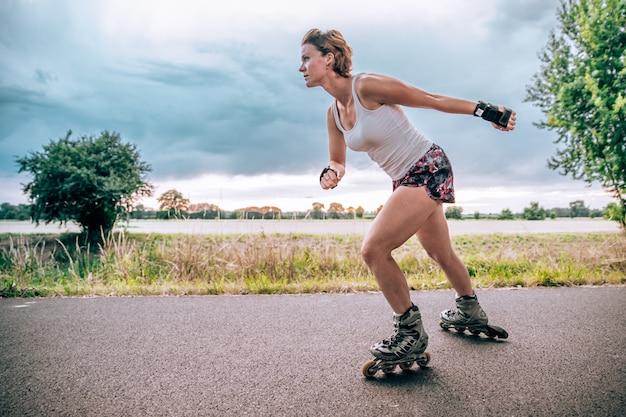 Joven monta en patines en un camino de asfalto fuera de la ciudad en verano