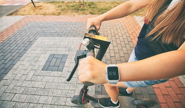 La joven está montada en el scooter eléctrico a través de la ciudad al atardecer por los caminos.