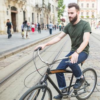 Joven montando bicicleta en la ciudad
