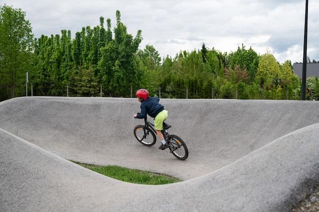 Joven montando una pista de bombeo con bicicleta bmx afuera en el deporte de adrenalina.