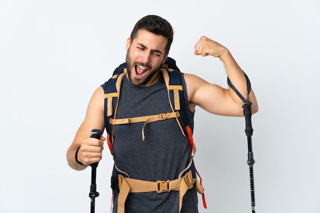 Joven montañero con una gran mochila y bastones de trekking aislados en blanco celebrando una victoria