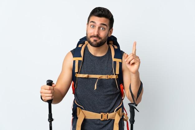 Joven montañero con una gran mochila y bastones de trekking aislados en blanco señalando con el dedo índice una gran idea