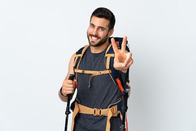 Joven montañero con una gran mochila y bastones de trekking aislados en blanco sonriendo y mostrando el signo de la victoria
