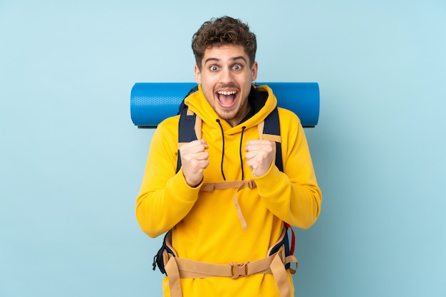 Joven montañero con una gran mochila en la pared azul celebrando una victoria