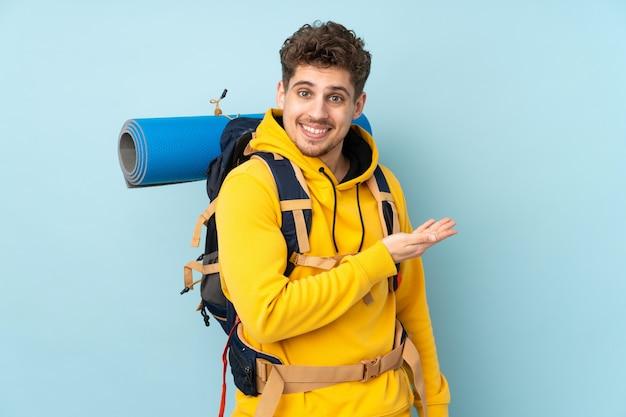 Joven montañero con una gran mochila en la pared azul extendiendo las manos hacia un lado