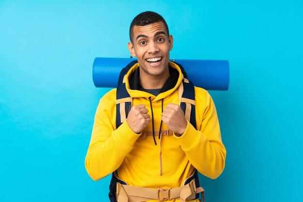 Joven montañero con una gran mochila sobre pared azul aislada celebrando una victoria