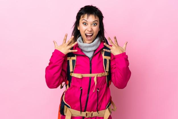 Joven montañero con una gran mochila sobre pared rosa con expresión facial sorprendida