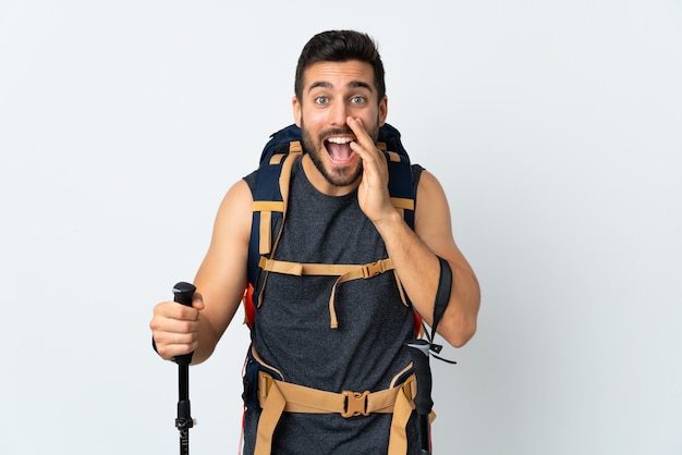 Joven montañero con una mochila grande y bastones de trekking aislados en blanco gritando con la boca abierta