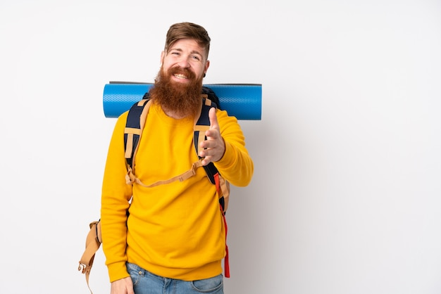 Joven montañero con una mochila grande sobre apretón de manos blanco aislado después de un buen trato