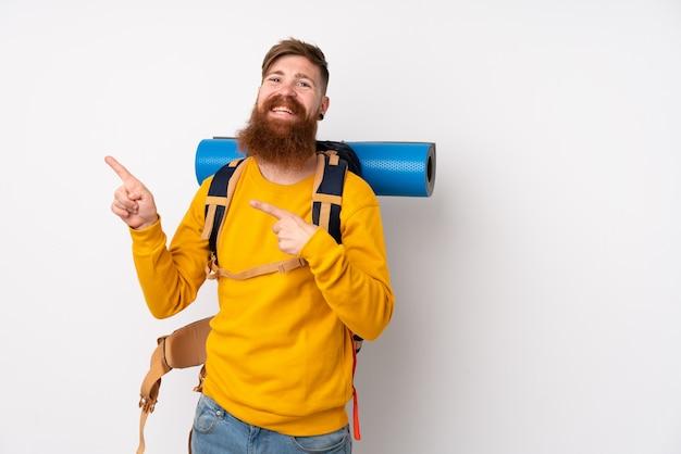 Joven montañero con una mochila grande sobre el dedo acusador blanco aislado al lado