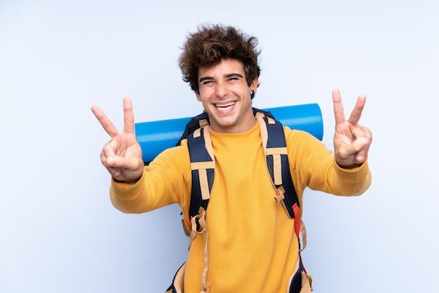 Joven montañero con una mochila grande sobre pared azul aislado sonriendo y mostrando el signo de la victoria