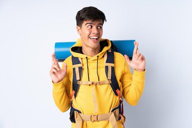 Joven montañero con una mochila grande sobre la pared azul con los dedos cruzados