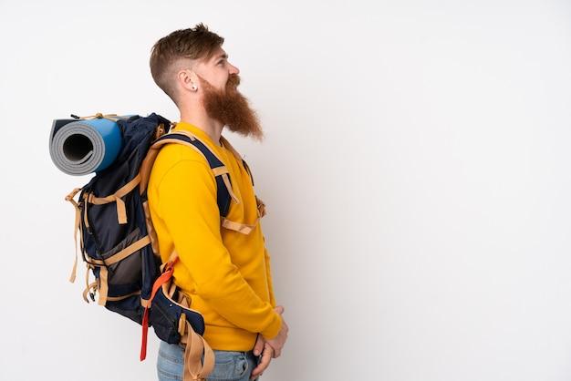 Joven montañero con una mochila grande sobre una pared blanca aislada mirando hacia el lado