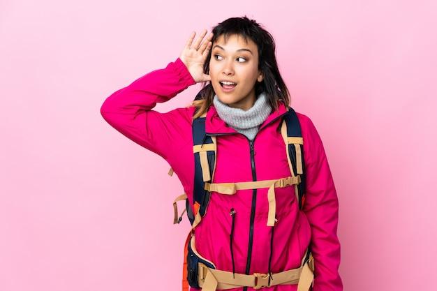Joven montañero con una mochila grande sobre pared rosa escuchando algo