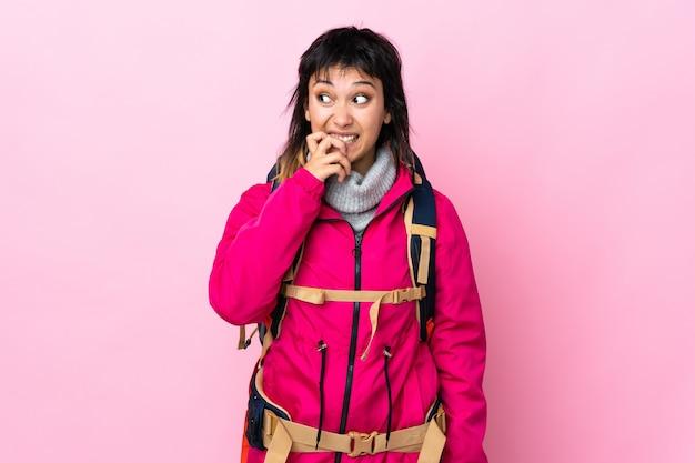 Joven montañero con una mochila grande sobre rosa aislado nervioso y asustado