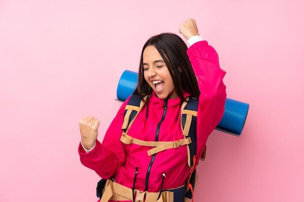 Joven montañero con una mochila grande sobre rosa celebrando una victoria