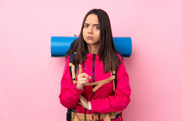 Joven montañero con una mochila grande sobre rosa frustrada y apuntando hacia el frente