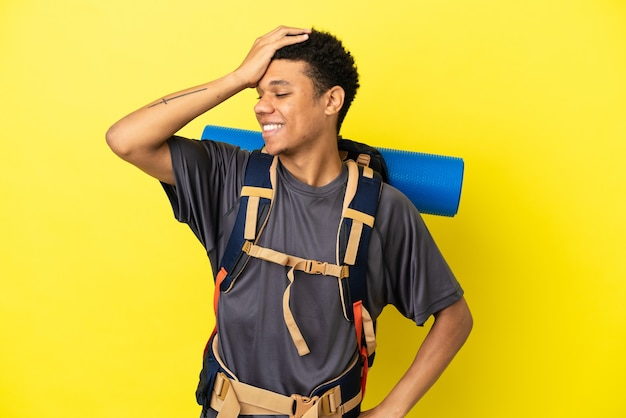 Joven montañista afroamericano con una gran mochila aislada sobre fondo amarillo se ha dado cuenta de algo y tiene la intención de la solución