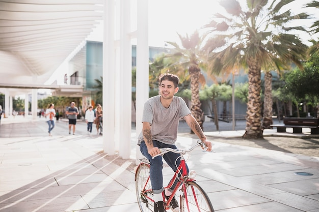 Joven montar bicicleta en el parque de la ciudad