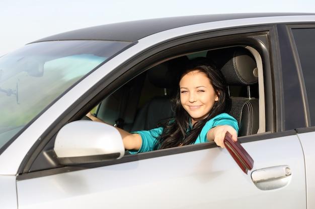 Joven morena al volante de la conducción muestra documentos