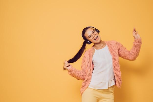 Joven morena alegre en gafas y auriculares en la cabeza vestida con suéter rosa blusa blanca y pantalones amarillos disfrutando de la música, cantando y bailando sobre fondo amarillo con espacio de copia.
