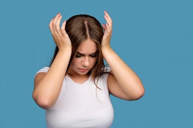 Joven morena en camiseta blanca que sufre de un dolor de cabeza, aislado sobre fondo azul.