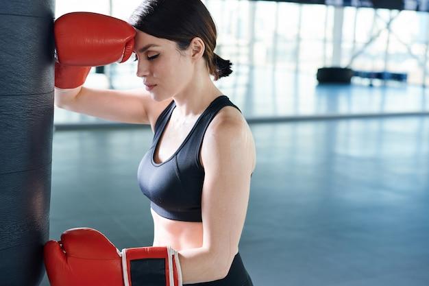Joven morena cansada boxeadora de pie junto a un saco de boxeo en el gimnasio mientras tiene un breve descanso antes del nuevo entrenamiento