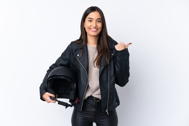 Joven morena con un casco de moto apuntando hacia un lado para presentar un producto