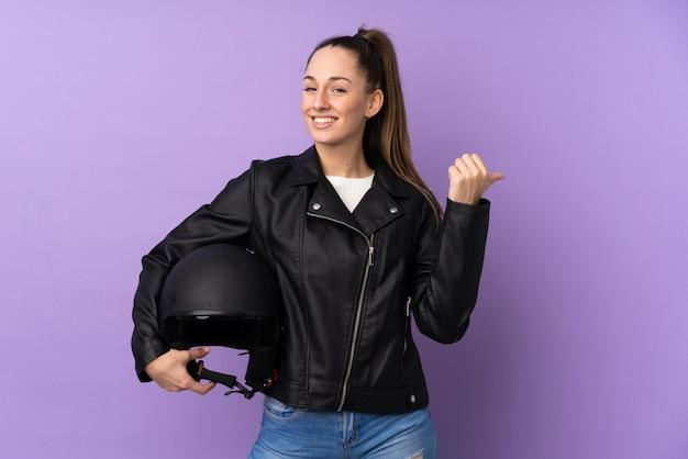 Joven morena con un casco de moto sobre pared púrpura aislado apuntando hacia un lado para presentar un producto