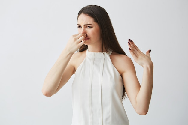 Joven morena cierre tapando la nariz. mal olor.