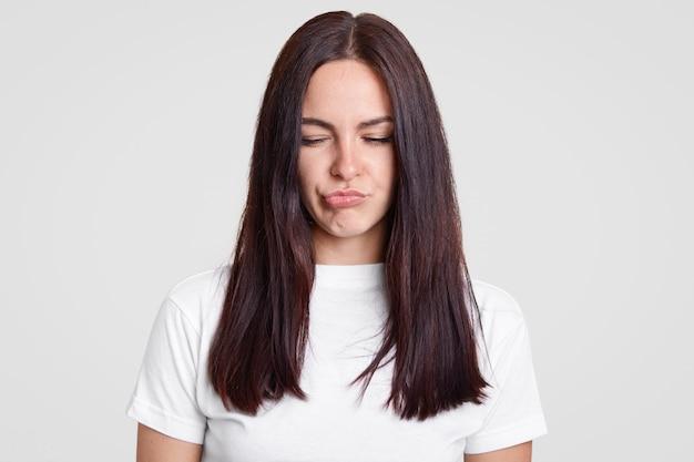 La joven morena disgustada frunce los labios, tiene expresión facial de descontento, escucha comentarios negativos sobre su trabajo