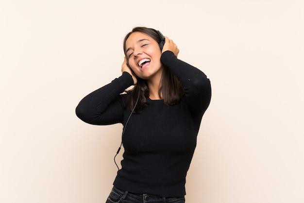 Joven morena escuchando música sobre pared aislada