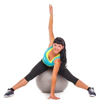 Joven morena feliz haciendo ejercicio con fitball