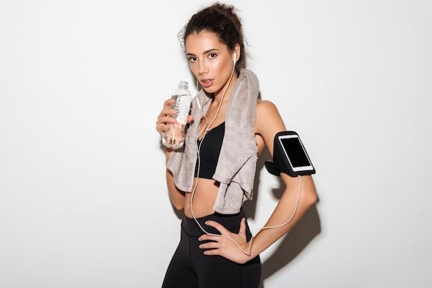 Joven morena fitness mujer con toalla sosteniendo el brazo en la cadera