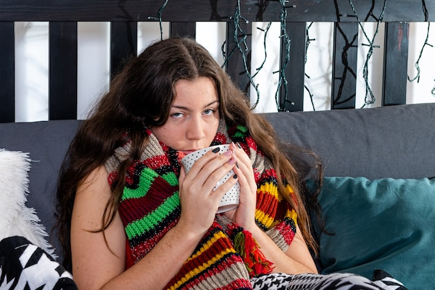 Joven morena fría con una bufanda caliente alrededor de su cuello sentado en la cama y bebiendo té caliente