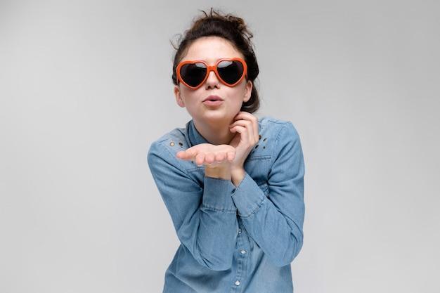 Joven morena con gafas en forma de un corazón. los pelos se recogen en un moño. la niña envía un beso al aire.