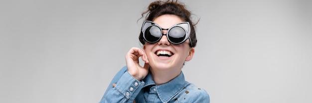 Joven morena con gafas negras. gafas de gato el cabello está recogido en un moño. la niña se llevó un dedo a la mejilla. la niña se esta riendo.