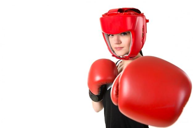 Joven morena en guantes de boxeo rojos y casco haciendo impacto