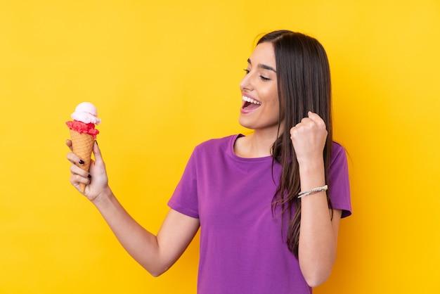 Joven morena con un helado de cucurucho sobre amarillo celebrando una victoria