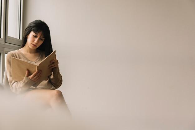 Joven morena leyendo cerca de la ventana