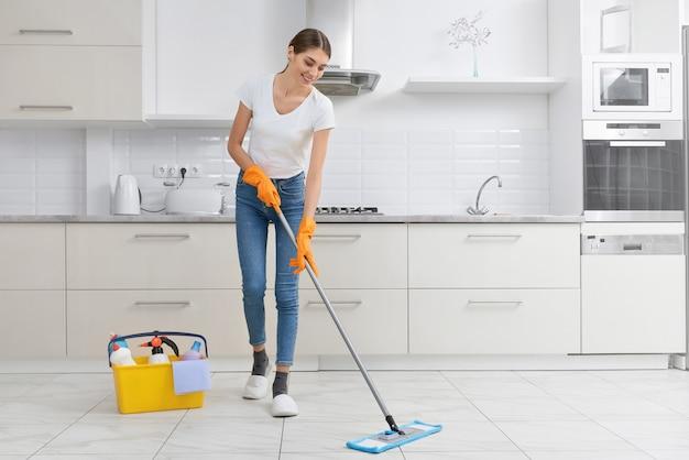 Joven morena limpieza piso de la cocina