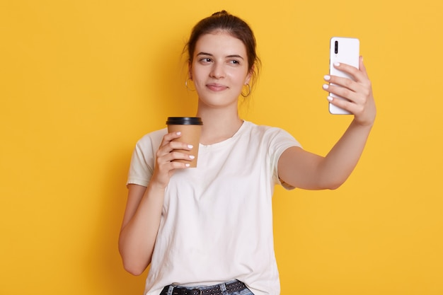 Joven morena con nudo sosteniendo café para llevar y tomando selfie a través de un teléfono inteligente moderno